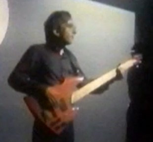 "James Warren (The Korgis) holding a Geoff Gale bass in the ""Everybody's got to learn sometime"" video"